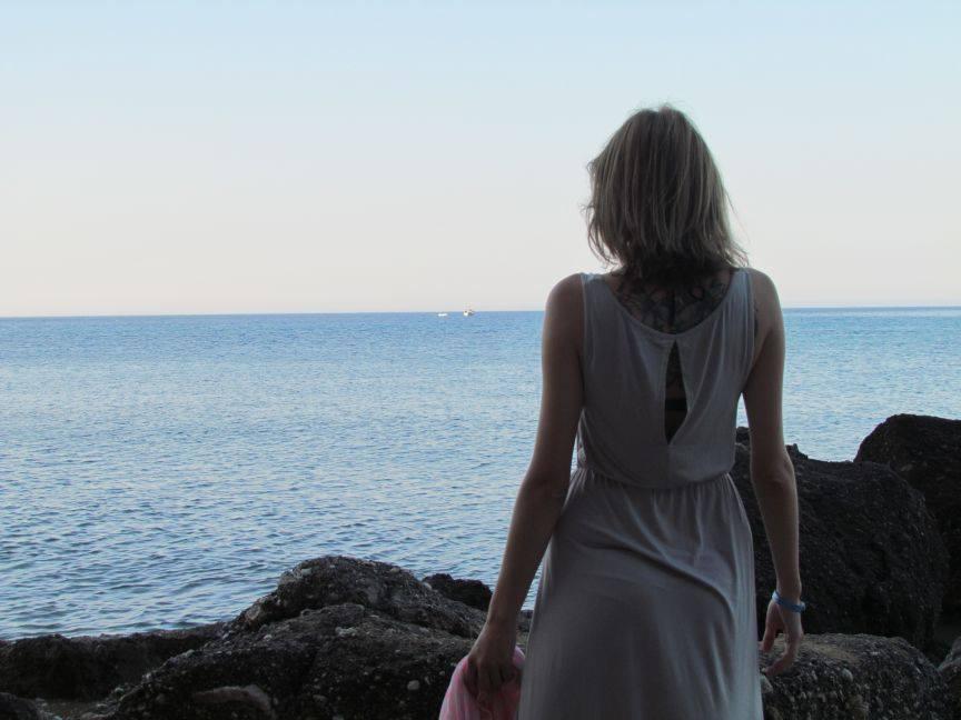 Bloggerin in Strandkleid steht auf das Meer blickend auf Felsen am Strand.