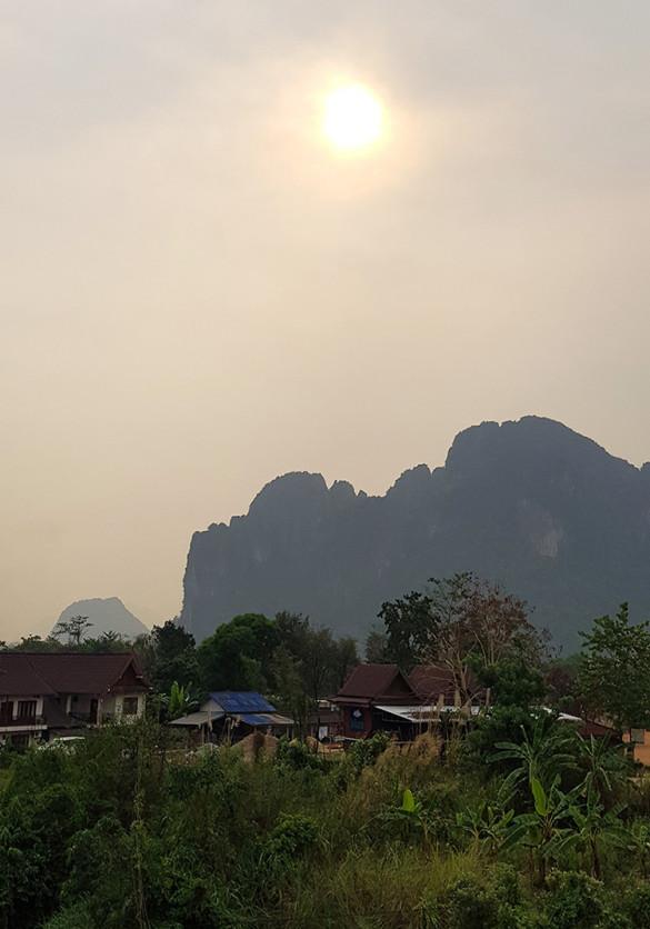 Blick auf die Landschaft in Vang Vieng - die Sonne verdeckt vom Rauch der Brandrodung