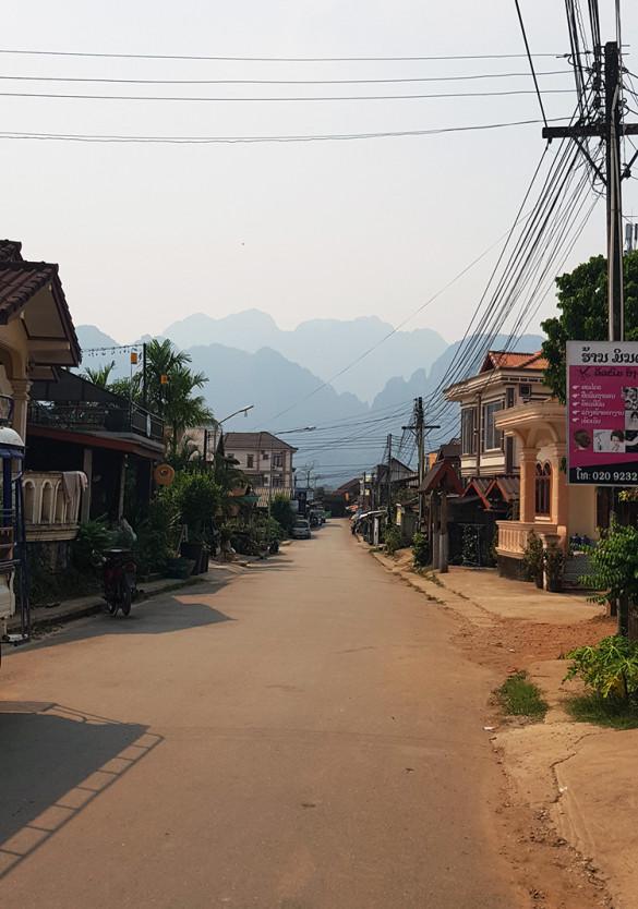 Blick auf eine Straße in Vang Vieng. Im Hintergrund Umrisse der Bergigen Landschaft.